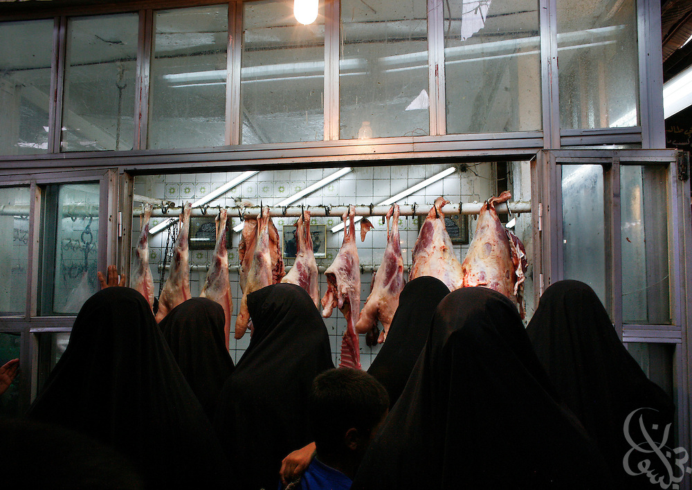 Iraqi women cue to buy meat from a local butcher August 21, 2006 in the Sadriya district market in Baghdad. As Iraqi fuel prices have risen, so to has overall inflation, with many basic food staples now costing double or more the price they were last year. .