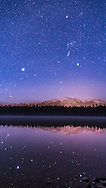 Orion and Canis Major over Lake Annette, in Jasper National Park, with Sirius and other stars reflected in the waters. Orion appears over Whistler peak, illuminated in part by lights from the Jasper townsite. <br /> <br /> I shot this on the morning of October 25, 2015, as the sky was brightening with dawn twilight. The exposure was 25 seconds at f/2.8 with the 24mm lens and at ISO 3200 with the Canon 6D. The camera was untracked, on a fixed tripod. No filter was employed - the fuzzy star glows come from high haze in the sky that morning.