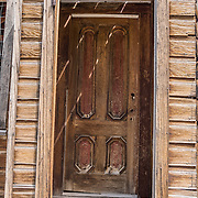 """A dilapidated wood door ages at Bodie, California's official state gold rush ghost town. Bodie State Historic Park lies in the Bodie Hills east of the Sierra Nevada mountain range in Mono County, near Bridgeport, California, USA. After W. S. Bodey's original gold discovery in 1859, profitable gold ore discoveries in 1876 and 1878 transformed """"Bodie"""" from an isolated mining camp to a Wild West boomtown. By 1879, Bodie had a population of 5000-7000 people with 2000 buildings. At its peak, 65 saloons lined Main Street, which was a mile long. Bodie declined rapidly 1912-1917 and the last mine closed in 1942. Bodie became a National Historic Landmark in 1961 and Bodie State Historic Park in 1962."""