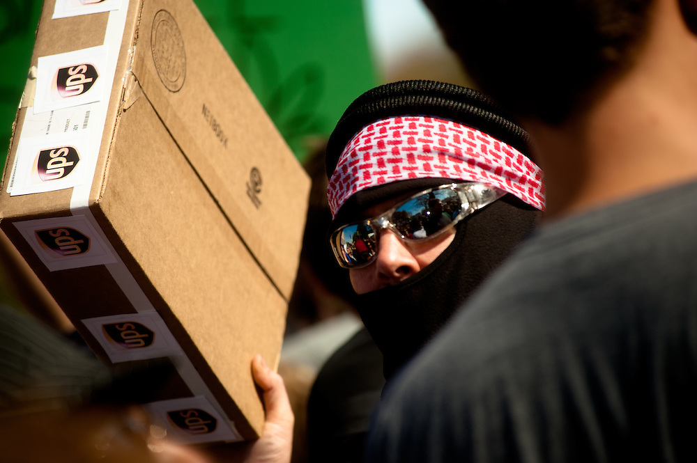 """Washington, DC, October 30, 2010 - Jon Stewert and Steven Colbert host the Rally To Restore Sanity and/or Fear.  Tens of thousands of ralliers donned costumes and carried signs.  Here, a """"terrorist"""" carries a UPS package."""