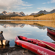 Red canoes and peaks of Sawtooth Wilderness reflect in Little Redfish Lake in Sawtooth National Recreation Area, Blaine County, Idaho, USA. The Sawtooth Range (part of the Rocky Mountains) are made of pink granite of the 50 million year old Sawtooth batholith. Sawtooth Wilderness, managed by the US Forest Service within Sawtooth National Recreation Area, has some of the best air quality in the lower 48 states (says the US EPA).