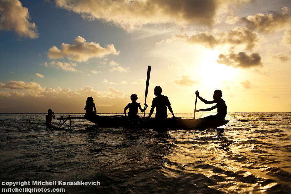 Boys in a canoe at sunset. Rah Lava Island, Torba Province, Vanuatu