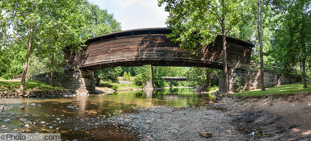 "Humpback Covered Bridge, built in 1857, is the oldest remaining covered bridge in the state of Virginia. Humpback Bridge is one of the few remaining covered bridges in the USA built higher in the middle than on either end (with a humpback 4 feet or 1.2 meters high). The bridge spans 109 feet (33 m) across Dunlap Creek (a tributary of Jackson River), near Covington, Virginia. Covered wooden bridges averaged ten times the lifespan of uncovered ones. Sometimes referred to as ""kissing bridges"" during the modest era of the late 1800s, covered bridges allowed horse and buggy passengers kissing privacy. Two former non-covered bridges here (built in the 1820s and 1838) were destroyed by floods, and a third bridge collapsed in 1856 due to heavy use and weathering. All three bridges were a part of the James River and Kanawha Turnpike, a heavily traveled mountain road that connected the Shenandoah Valley with the Alleghany Mountains and westwards. The decking, unlike houses and other structures, could not be painted to prevent deterioration, as the traffic from horses and wagons would quickly remove any available paints of the era. The Humpback Covered Bridge was used from 1857 to 1929, when a steel truss bridge was built for US Highway 60 immediately to the north. The bridge was listed in the National Register of Historic Places in 1969. The bridge retains most of its original 1857 hand-hewn white oak and hickory support timbers and decking, but most of the walls and roofing have been replaced several times. The supports incorporate a unique curved multiple kingpost-truss system that is not found in any other surviving wooden bridge in the USA. The bridge is a unique design not duplicated anywhere else. How to reach Humpback Bridge: Take Exit number 10 off of Interstate 64 in Virginia and follow signs, 1 mile east. It is 3 miles west of Covington, Virginia adjacent to U.S. Highway 60 off Rumsey Road (SR 600). Panorama stitched from 7 overlapping images."