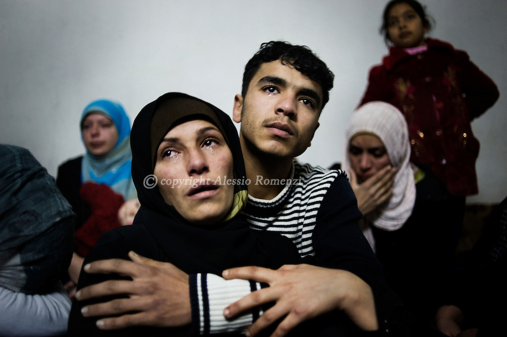 SYRIA - Homs province: One mother and her son cry the lost of the her other two sons, killed by a mortar attack launched by Al Asad forces, in Homs province on February 20, 2012. ALESSIO ROMENZI