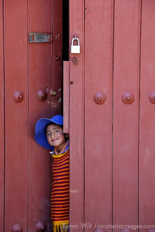 South America, Bolivia, Calamarca. Boy peeks through door in Calamarca.