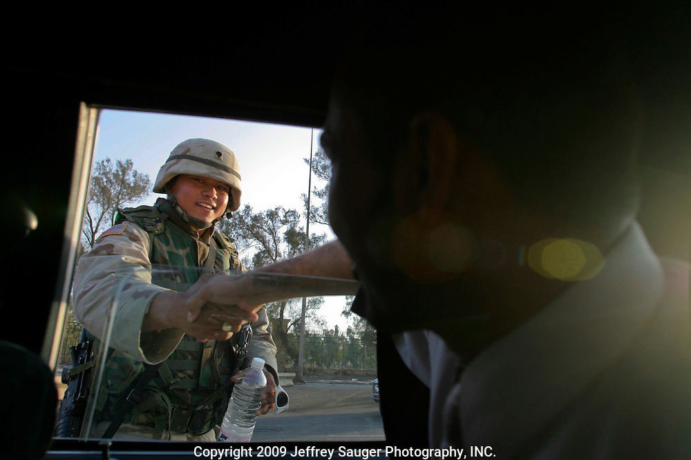 Emad Al-Kasid shakes hands with a U.S. soldier at a checkpoint  in Baghdad, Iraq, Tuesday, July 22, 2003. The Al-Kasid family is traveling back to its home in Nassiriyah, Iraq, for the first time since 1991 after fighting in the failed uprising against Saddam Hussein, fleeing to a refuge camp in Saudi Arabia for 3 years and finally settling in Dearborn, MI.