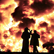 Belfast, July 12, 2004 - Friends share a drink while watching a bonfire in the Westland district of Belfast, Northern Ireland on the morning of July 12, 2004.  Bonfires are lit across Northern Ireland to commemorate the 1690 Battle of Boyne.