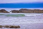 Landscape photo of ocean waves  rolling into shore along the Oregon Coast near Yahats .