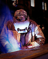 Welder in engineering fabrication yard working.