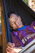 Man, asleep, western dress, hammock, Akha; Chiang Mai; Hill Tribe Village; Thailand