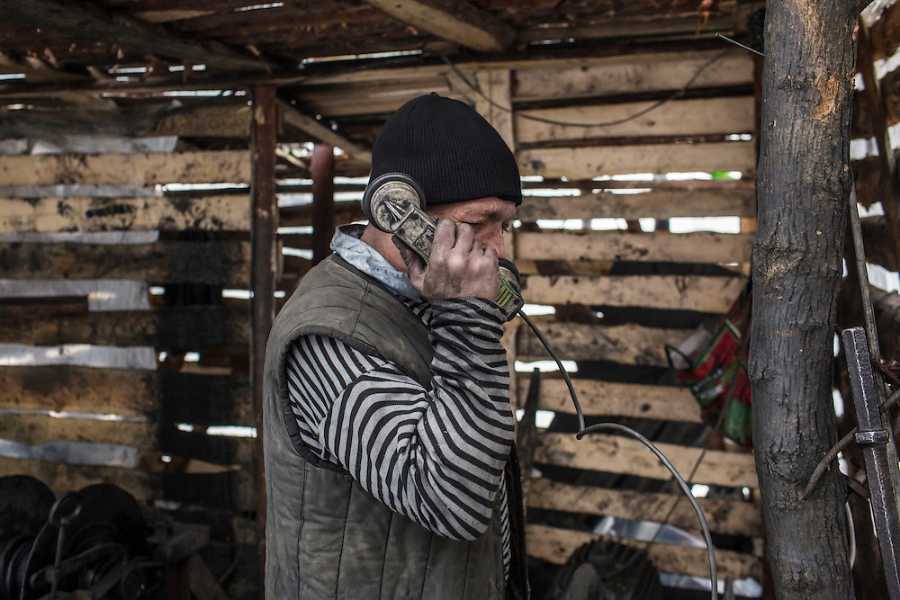 SNEZHNE, UKRAINE - JANUARY 25, 2015: Sergei Danshin, who works at a small private coal mine, talks on the radio to miners working down in the mine in Snezhne, Ukraine. The mine produces approximately 15 tons of coal per day with a crew of four men. CREDIT: Brendan Hoffman for The New York Times