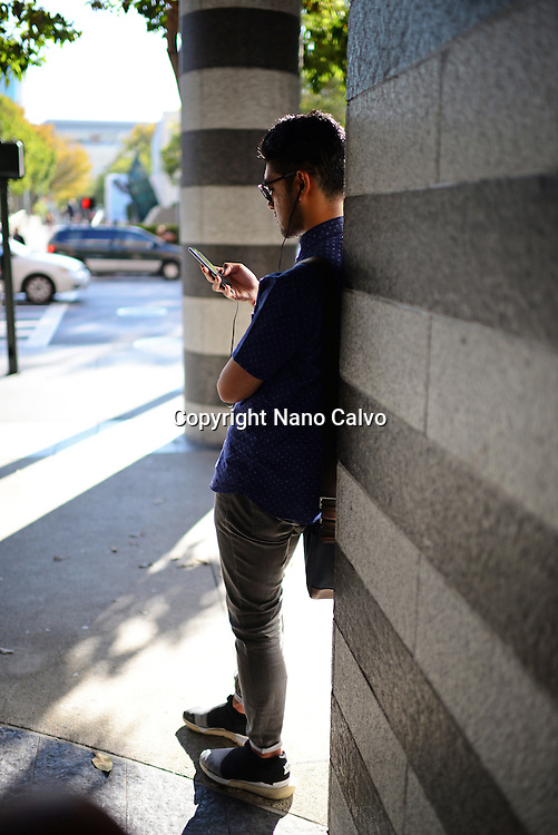 Young man using smartphone outside San Francisco MoMA.