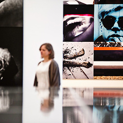 London, UK - 8 October 2012: a woman walks by at pictures by Daido Moriyama. The exhibition examine the relationship between the work of William Klein (b.1928) and that of Daido Moriyama (b.1938). Taking as its central theme the cities of New York and Tokyo, the show explores both artists' celebrated depictions of modern urban life.