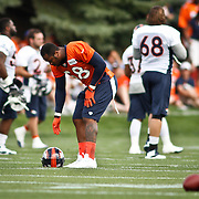 SHOT 7/25/13 9:26:46 AM - The Denver Broncos Von Miller #58 reaches down for his helmet as he prepares to run through drills during opening day of the team's training camp July 25, 2013 at Dove Valley in Englewood, Co. Miller is appealing a possible four game suspension with the league. (Photo by Marc Piscotty / © 2013)