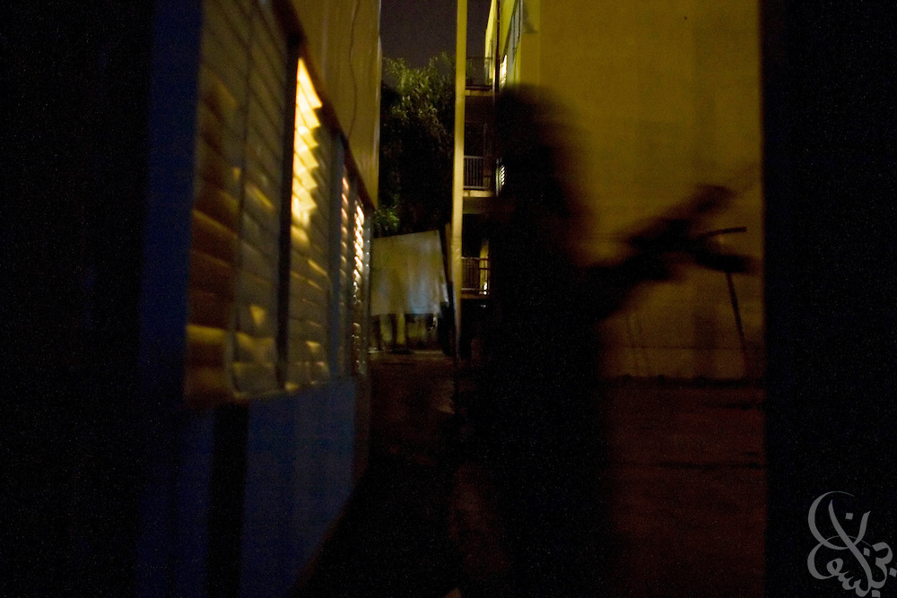"An armed Jamaican gang member moves through a public housing project December 25, 2008 in a section of the gang-controlled Rema ""Garrison."" Gunmen in the garrisons are well armed with weapons flowing in from Colombia, Haiti and the United States and this abundance of guns is certainly one of the factors fueling Jamaica's high murder rate."