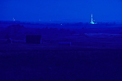 Stock photo of a lighted on-shore rig in the distance