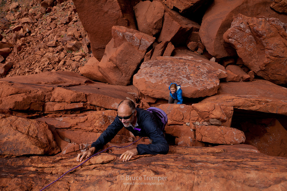 Paul Diegel, getting past an obstacle while exploring a remote area in Glen Canyon National Recreation Area, Utah