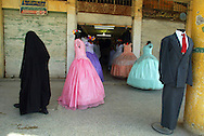 A woman garbed in a black robe, the traditional Muslim outfit worn by most women in the area walks past festive party dresses at a local shop in the town of Hindia, Iraq, Sunday June 8, 2003. A  strengthened  fundamentalist rule of Islamic law has filled the power vacum left by the toppled regime of Saddam Hussein, who during his government supressed opposition from the Shiite Muslim.