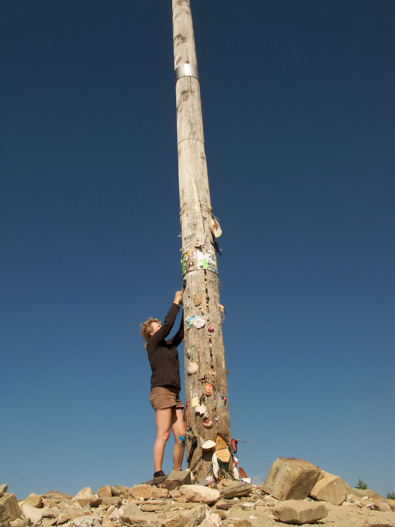 A pilgrim attaches a note to the Iron Cross. The Iron Cross, or Cruz de Ferro, is a highly emblematic place on the Camino de Santiago where walkers leave mementoes and stones. It is at 1504m above sea level.