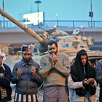 Anti government protesters pray in front of a tank on the front line with pro-Mubarak demonstrators in Tahrir Square in Cairo, Egypt. February 2011.