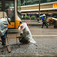 China, Chongqing, Road workers dig up city street by hand using hammers and chisels on rainy autumn afternoon