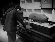 """Visitors to the Edo Museum read about an unexploded bomb from WWII air strikes found in Tokyo, on display at the Edo Museum.  Bombs are still occasionally dug up at central Tokyo construction sites, so many were dropped on the city during the war.  It is understood that the Edo Museum documents Tokyo history (Edo was the name for Tokyo before it became the """"East Capital"""" [東京] of Japan.)  Still, this permanent exhibit at Tokyo's Edo Museum, with no meaningful context offered about the bigger war, leaves the museum visitor impression that Japan was the sole, innocent victim of that massive war."""