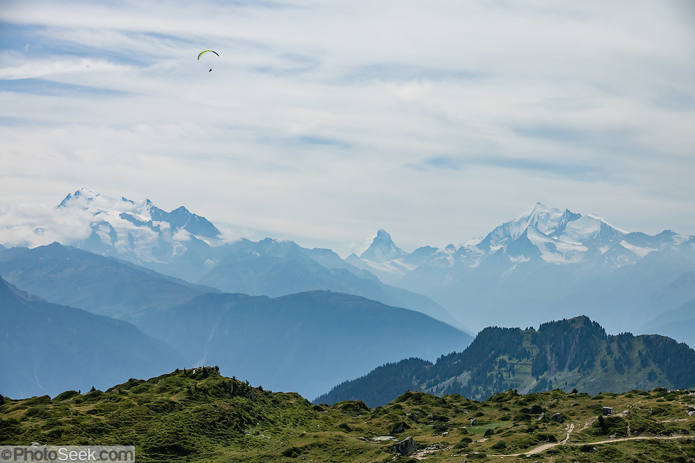 """See the Dom, Matterhorn and Weisshorn (left to right) from Riederalp ridge, in the Pennine Alps, Valais/Wallis canton, Switzerland, Europe. The Dom (4545 m / 14,911 ft) is the third highest mountain in the Alps and the second highest in Switzerland (after Monte Rosa). Located in the Pennine/Valais Alps between Randa (in Matter Valley) and Saas-Fee, the Dom is the main summit of the Mischabel Group (German: Mischabelhörner), the highest massif lying entirely in Switzerland. The Mischabel Group (ancient German term for pitchfork) includes many summits above 4000 meters: the Nadelgrat, composed of the Lenzspitze, the Nadelhorn (4327 m/14,196ft """"Needle Peak""""), Stecknadelhorn, Hohberghorn and Dürrenhorn; and Täschhorn (4491 m south/just left of highest peak in photo), plus the flat summit of the Alphubel (4206m / 13,799ft, further left). From Fiesch, lift to Fiesheralp, then hike to vast views of Aletsch Glacier via Hohbalm, Moosfluh, Hohfluh, Riderfurke, and Riederalp."""