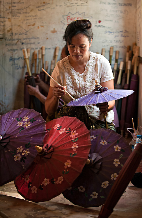 A woman painting hand made umbrellas in Shwe Patto village, Shan State, Myanamr.