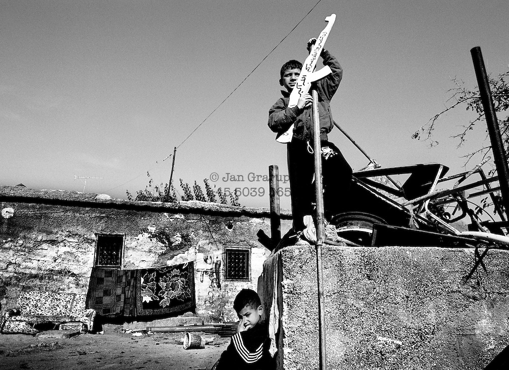 Small boys waiting for a funeral procession; they have acquired yet another martyr. <br /> Nov. 2002