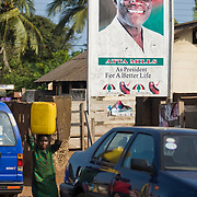 A girl carrying a jug of water walks past a billboard advertising National Democratic Congress (NDC) candidate Atta Mills ahead of the upcoming presidential elections in Accra, Ghana on Monday September 8, 2008.