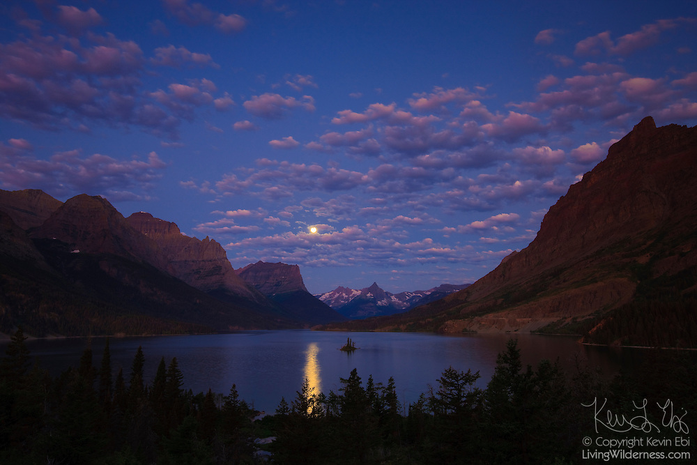 The full moon shines above St. Mary Lake, the second largest lake in Glacier National Park, Montana, about a half hour before sunrise. The glint of the full moon falls next to Wild Goose Island.