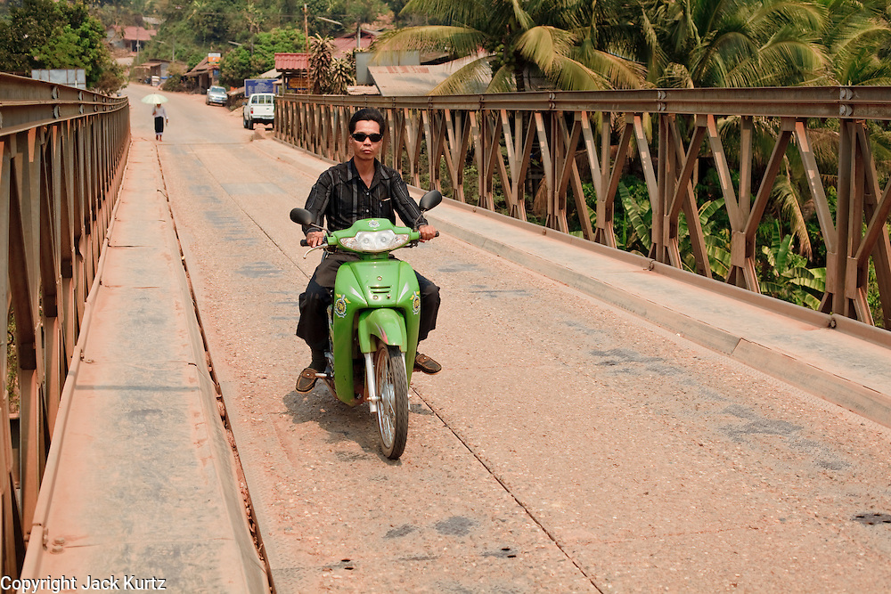 Mar. 12, 2009 -- VIENTIANE, LAOS: A motorcyclists crosses a one lane bridge on the Nam Lik River near Vientiane, Laos. PHOTO BY JACK KURTZ