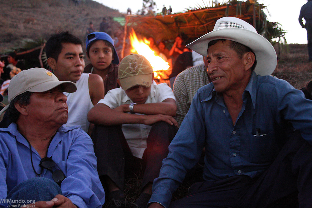 Julián Sánchez Chen (right), who lost his wife and children at the Pak'oxom massacre, tells his testimony about the events to students from the Nueva Esperanza Institute (founded by Rio Negro survivor Jesus Tecú Osorio) at the site of the mass killing on the twenty-seventh anniversary of the event. On March 13, 1982, the Guatemalan army and civil patrolmen from neighboring Xococ rounded up residents of Rio Negro, marched them uphill to Pak'oxom, and brutally raped and massacred 177 women and children. Nearly 400 community members of Rio Negro were killed in four separate massacres in the early 1980's due to the community's resistance to give up their lands and make way for the Chixoy hydroelectric project. After finding life in the Pacux resettlement village unsatisfactory, Julián Sánchez Chen came back to reestablish the Rio Negro community along with his cousin Sebastian Iboy Osorio and Mario Chen Rojas on May 18th, 1991. For nearly a decade (1982-1991), the village of Rio Negro was wiped out of the map. Pak'oxom Peak near Rio Negro, Rabinal, Baja Verapaz, Guatemala. March 13, 2009.