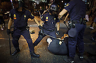 Riot police barton charge over a protestor at Cibeles Square during a demonstration against the Spanish government, on Thursday, July 18, 2013, in Madrid, Spain. Thousands demonstrators demanding the resignation of Prime Minister Mariano Rajoy and its party gathered in front of the People's Party headquarter. Rajoy rejected demands to resign after more alleged secret payments and test messages related to former political party treasurer Luis Barcenas under investigation appeared. The spectacle of alleged greed and corruption has enraged Spaniards hurting from austerity and sky high unemployment.