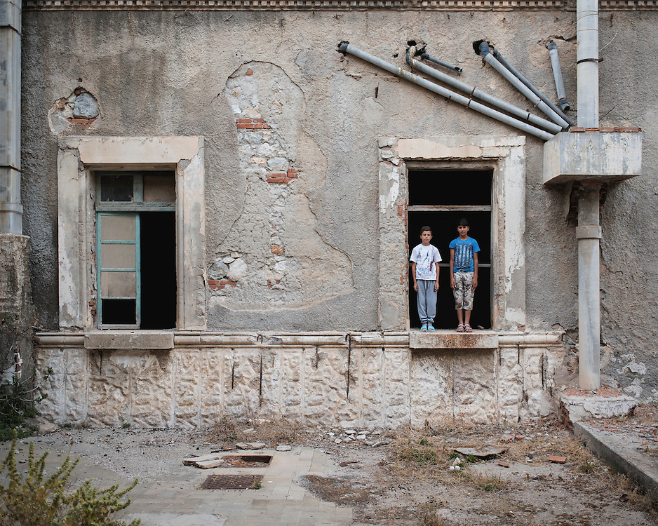 Kurdish refugee children, Youssef, 14, and Diar, 13, standing in a window at the abandoned Lepida psychiatric hospital, in whose grounds the Leros &lsquo;Hot spot&rsquo; (an EU-run migrant&rsquo;s reception centre) has been built. <br />