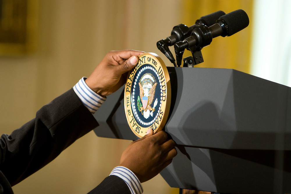 An aide hangs the presidential seal on the podium prior to President George W. Bush's remarks commemorating Military Spouse Day in the East Room at the White House in Washington, DC, on Friday, May 11, 2007.