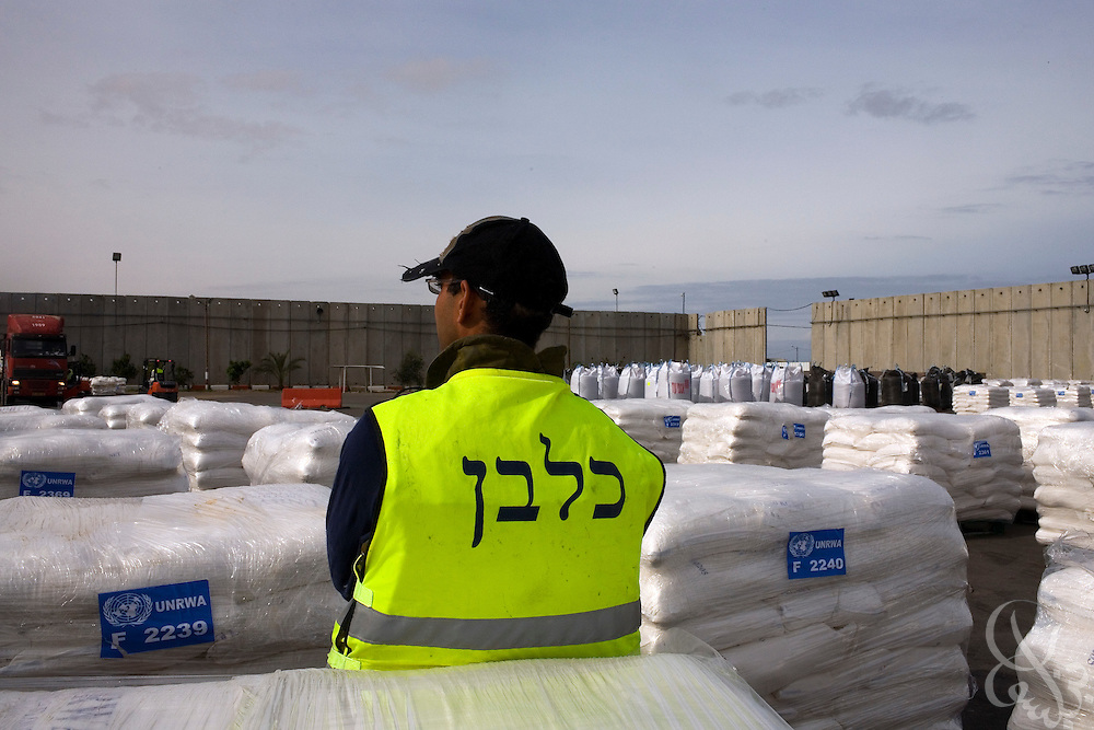 An Israeli security services agent stands watch over United Nations Aid shipments awaiting delivery at the Karem Shalom border crossing with Israel/Gaza January 8, 2009. The United Nations announced it was halting shipments of aid into Gaza today after one of its' drivers was fired on and killed by Israeli forces as he drove to pick up aid shipments on the Gaza side of the border.
