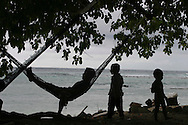 A family relax near the beach on the island of Kiribati in the South Pacific. The islands, and their way of life, are endangered by rising sea water levels which are eroding the fragile atoll, home to approximately 92,000 people.