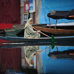 A young Kashmiri paddles on Dal Lake in Srinagar.