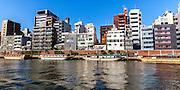 Buildings and boats alongside the Sumida River, Tokyo, Japan.