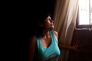 Ruth Collas looks out the window of her home on Monday, Apr. 6, 2009 in Ventanilla, Peru.