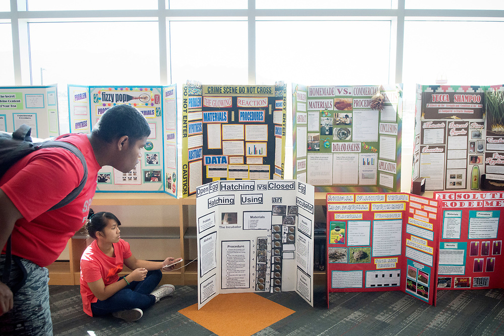 mkb032317/metro/Marla Brose --  Avery Tenorio, left, a senior at Bernalillo High, checks out some of the Bernalillo High science fair project displays near Rezeile Acantilado, (cq) second from left, an 8th grader who is helping with the science fair, as other students present their projects to judges in the school's library, Thursday, March 23, 2017, in Bernalillo, N.M. (Marla Brose/Albuquerque Journal)