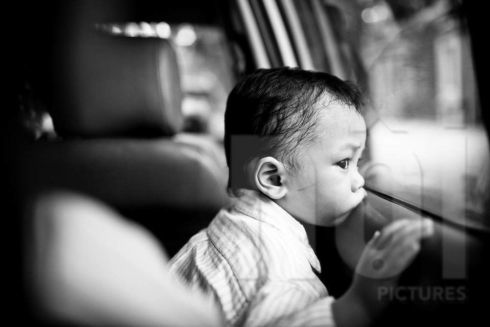 Four year old Nguyen Van Tien rests his mouth on a car window-sill as he observes the city passing by outside, Hanoi, Vietnam, Southeast Asia