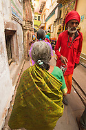 Back alleys of Varanasi on the way the Ganges are lined with colorful saris, temples, and groups of worshipers