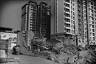 Old makes way for empty shells of the new.  A woman resident locks her bicycle in front of her house, the last remaining of her neighborhood on the block beside the ruins of her neighbor's house, as a the empty shell of a huge new apartment block stands unfinished, without a significant construction crew in sight.   In Xingtai, there are huge complexes, standing unfinished or sparsely occupied.  This is an unusual sight in this country that has enjoyed double digit-growth for three decades.  Xingtai, Hebei Province, China.