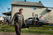 Children play on their dad's demolition derby car outside of their home in West Aliquippa, Pennsylvania, USA on May 8, 2015.<br /> <br /> Since 1987, the city has been designated as a distressed municipality under the state's Act 47, a law that created a recovery program that's helped some 29 municipalities in the state stay afloat.<br /> <br /> The city now has fewer residents now than the local steel mill had employees (14,000) in its heyday. The mill closed for good 20 years ago. <br /> <br /> With few good job opportunities available, children who grow up in the area may be faced with tough economic times when they are ready to join the workforce.