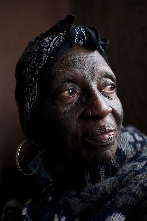 Agatha Moore, 77, lives on the 7th floor with her son, Jordan Moore, 37, who works for the government as a street sweeper. Ms. Moore cannot climb the stairs, and therefore cannot leave her sparse apartment. She spends her days reading a worn Bible.