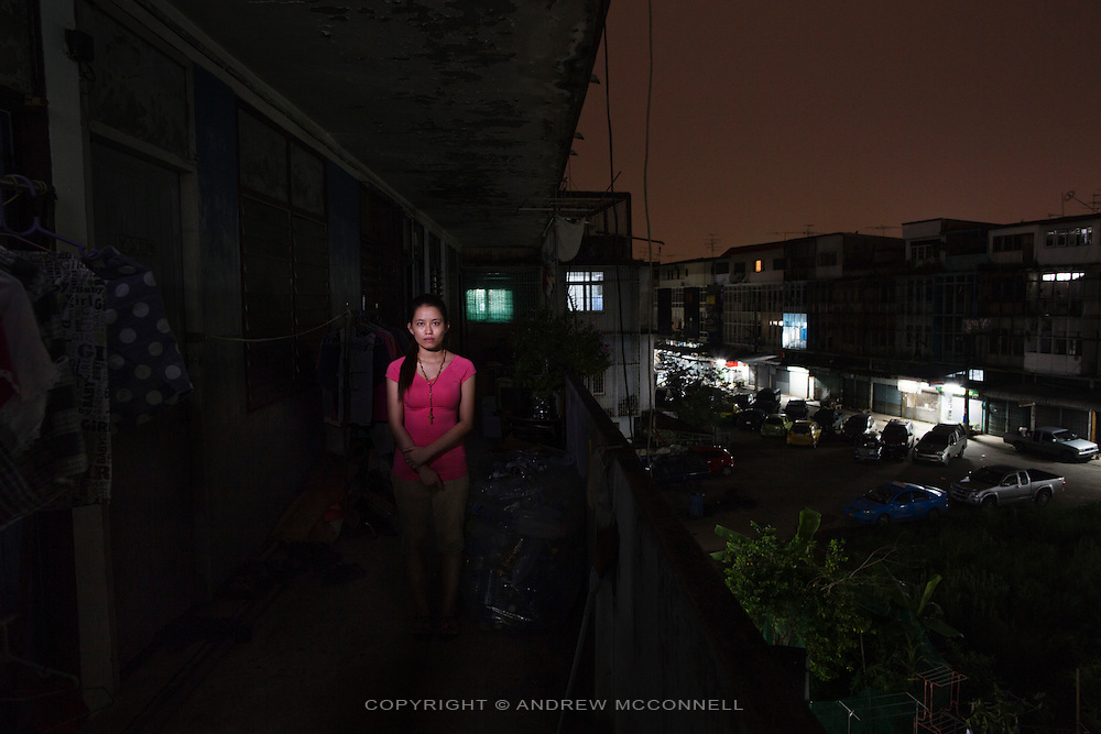 Vietnamese refugee Nguyen, 21, from Con Dau, pictured at her apartment block in Bangkok, Thailand.<br /> <br /> &quot;Because I'm living in a Catholic parish in Con Dau, Da Nang, the Da Nang government wanted to close the parish and take the land away from the people. On May 4th, 2010, there was a funeral of Mrs Dang Thitan, a local woman from the village. The government had refused to allow the funeral to take place so when we brought her coffin to the cemetery the police appeared and they prevented us from entering the cemetery. At that time the people sat around and read the bible but then police reinforcements arrived and started beating the people. The severely attacked the villagers, even pregnant women, they had batons and electric rods. They arrested around 60 people from the parish included my mother, at the end they took away the coffin and left the village in chaos. <br /> <br /> After that all the villagers ran away, some to other parts of Vietnam. The government thought anyone who fled outside were enemies of the country. I went to Laos without any notification to police. I was among the people who threw the muck at the police, they took video so they had my name. Because people resisted the government labelled our village as against them. They wanted to close down the whole village and take away the church and the cemetery. For a long time they don't like the Catholic parish because we had very strong religious belief. In history our village supported the southern government and that's why they don't like these Catholic villages. If you are Catholic you can't work for the government, you have to give up your religion first. We are discriminated against, our village was always overlooked by government.<br /> <br /> My mum was held for 6 months, then sentenced her to home arrest for 9 months, now she has a heart problem because of what happened to her. They thought she was the one who incited violence and they beat her in prison. They follow her now ever
