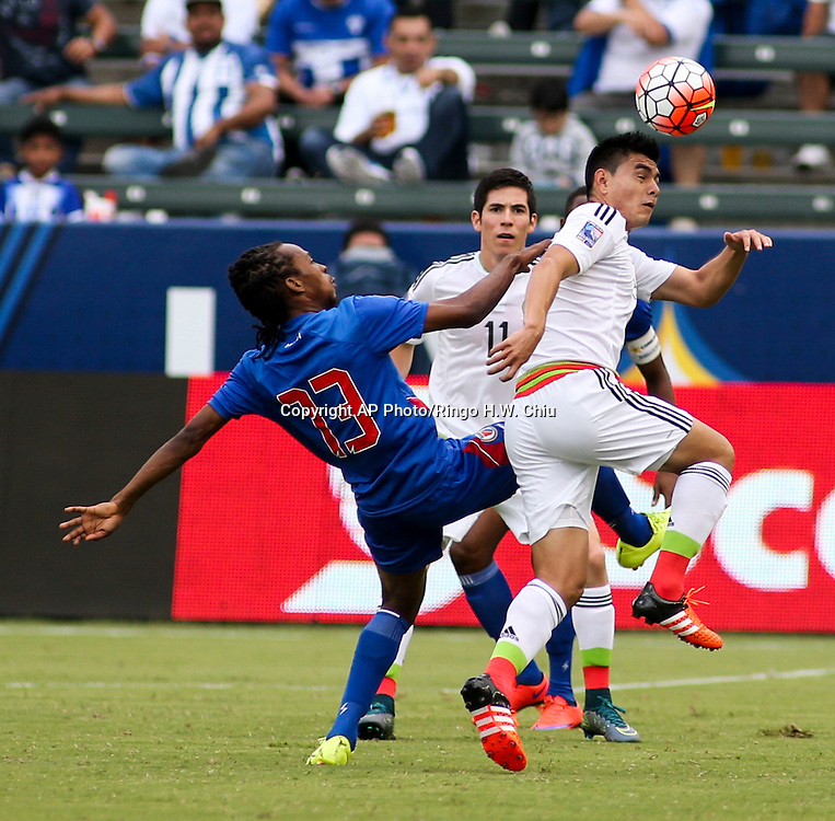 Mexico midfielder Luis Guadalupe Loroña Aguilar #19, right, heads the ball away from Haiti midfielder Venel Saint Fort #13 in the first half of a CONCACAF men's Olympic qualifying soccer match in Carson, Calif., Sunday, Oct. 4, 2015. (AP Photo/Ringo H.W. Chiu)