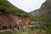 Passengers get off the train as workers clear a small landslide from the tracks.